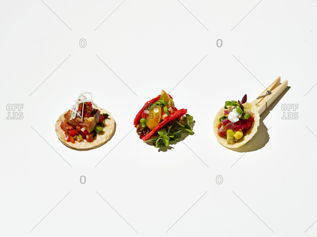 Three different tacos on white background