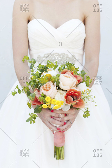 Mid section view of bride holding colorful bridal bouquet