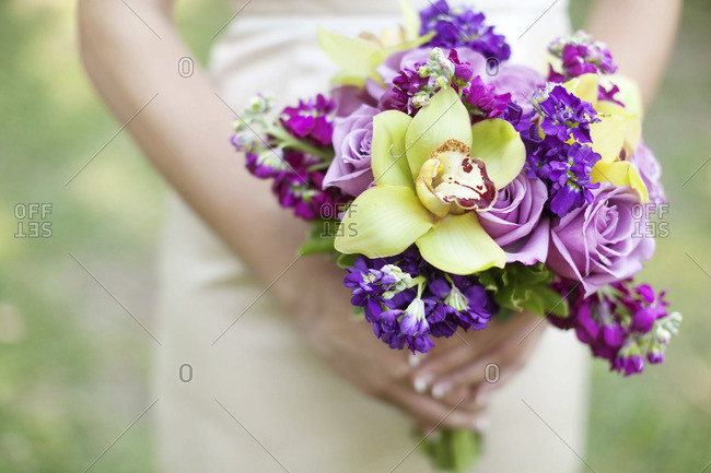 Mid section view of bride holding purple and green bridal bouquet