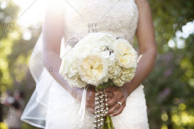 Mid section view of bride holding white bridal bouquet