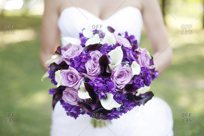 Mid section view of bride holding purple and white bridal bouquet