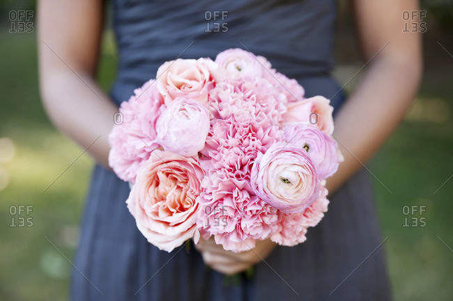Mid section view of bridesmaid holding a pink variation bouquet