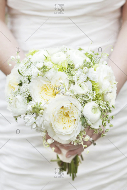 Mid section view of bride holding white peony bridal bouquet
