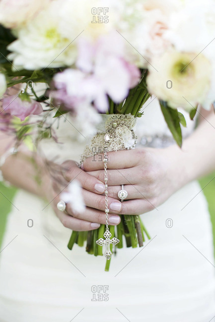 Mid section view of bride holding pale bridal bouquet