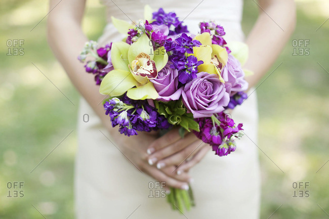 Mid section view of bride holding bridal bouquet