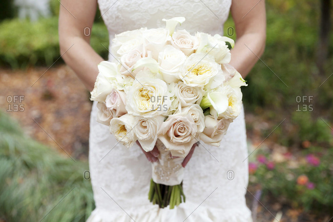 Mid section view of bride holding pale pink and white bridal bouquet