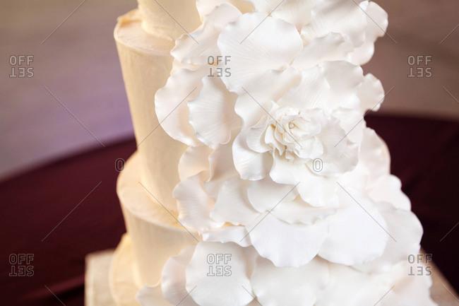 White cascade of rose petals on a wedding cake