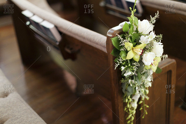Wedding bouquet of orchids and roses on a chapel pew