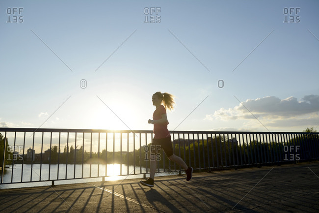 Young woman jogging over bridge at back light