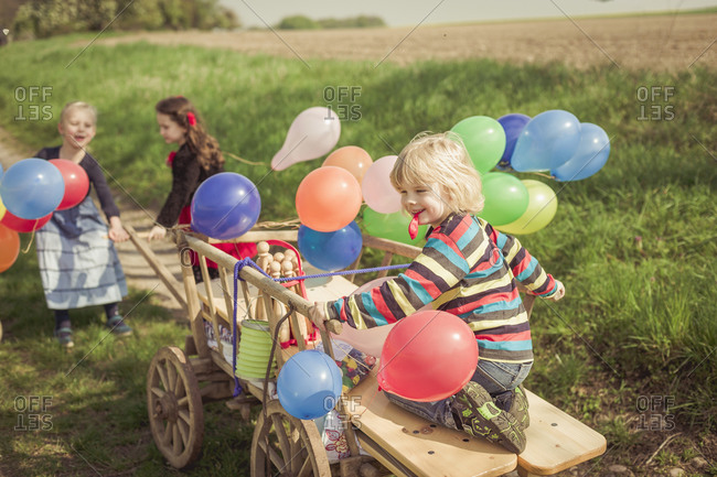 Children on the move with wooden trolley and balloons