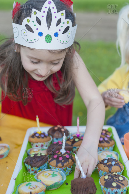 Little girl with birthday muffins
