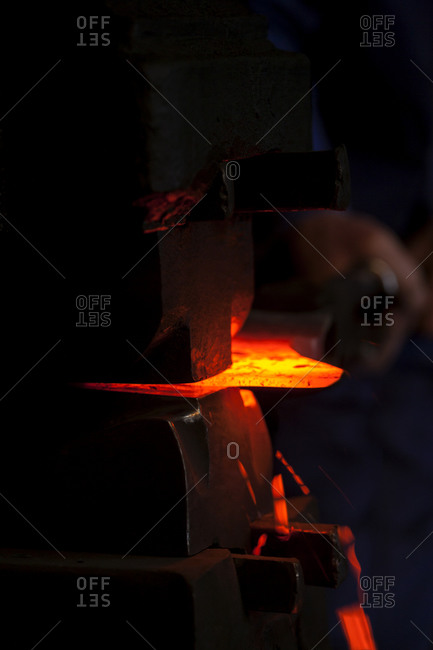 Blacksmith working on glowing axe at historic blacksmith's shop, Josefsthal, Bavaria, Germany
