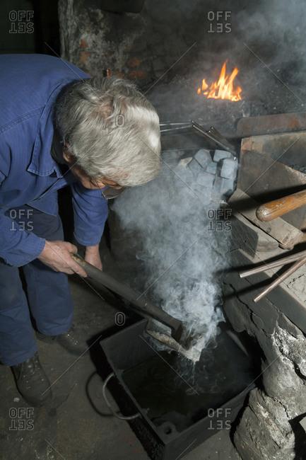 Blacksmith at work in historic blacksmith's shop