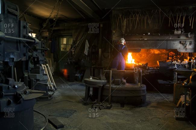 Senior blacksmith at work in blacksmith's shop