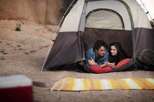 Camping couple lying in a tent