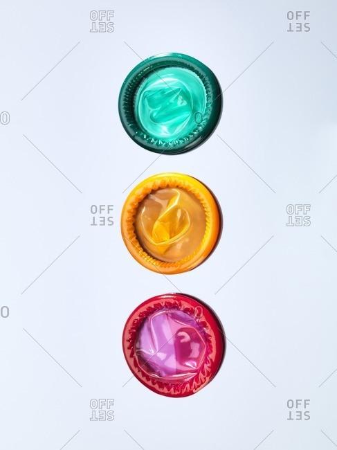 Three brightly coloured condoms, studio shot