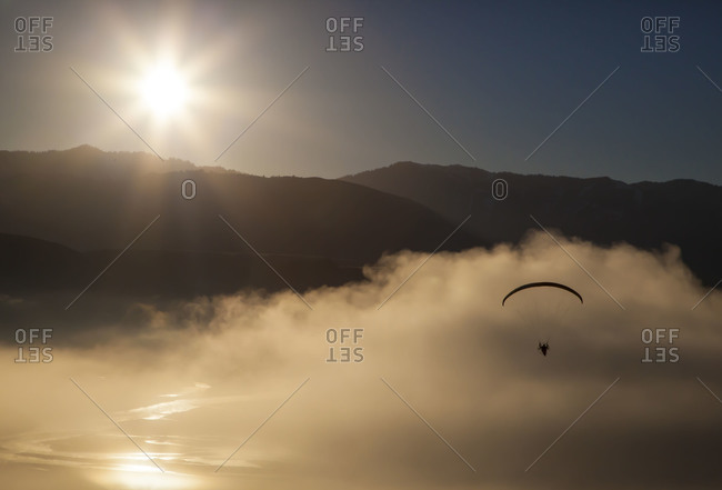 A paramotor pilot flies over the Snake River just after sunrise, south of Jackson Hole Wyoming