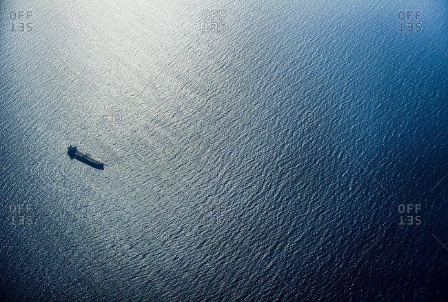 A cargo ship sailing across a vast blue ocean in the late afternoon