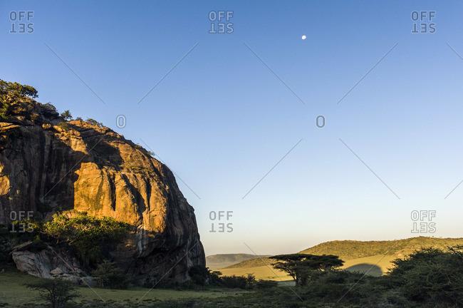 Moonrise at dawn over a rocky outcrop on the savannah plain