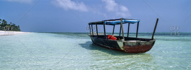 A fishing boat moored beside a stretch of deserted tropical beach