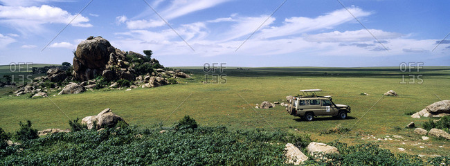 A safari beside rocky granite outcrop known as a kopje on a short grass savannah plain