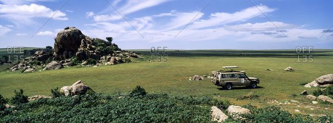 A safari beside rocky granite outcrop known as a kopje on a short grass savannah plain