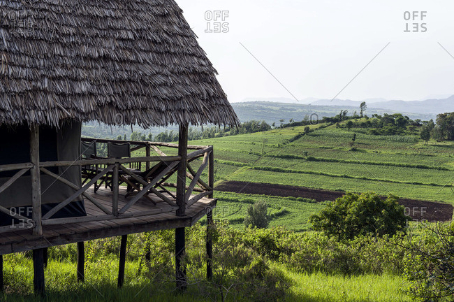 A thatched roof safari tent and balcony overlooking rich farmland on a hillside