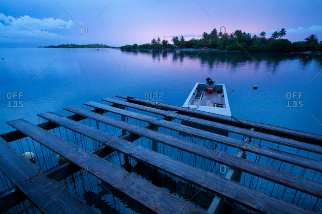 A boat is tied up to an oyster platform on a Tahitian pearl farm at the end of a calm day.