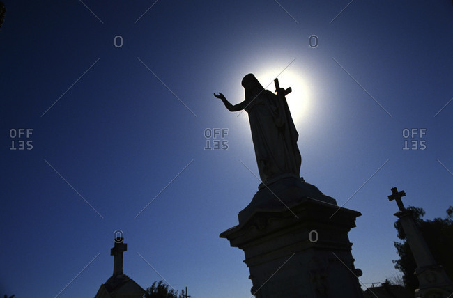 Silhouette of sculpture in cemetery