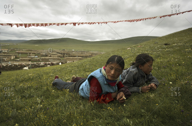 Qinghai, China - July 21,2006: Girls resting on a hill in a small remote town