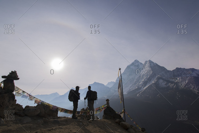 Prayer flags mark the top of a small trekking peak above Dingboche in the Everest region of Nepal. Two trekkers reach the top to watch the sunrise over Ama Dablam