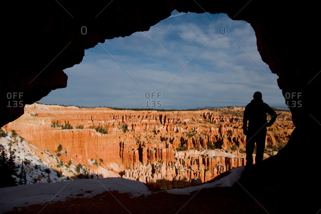 A woman looks out at the Bryce Amphitheatre at sunrise.