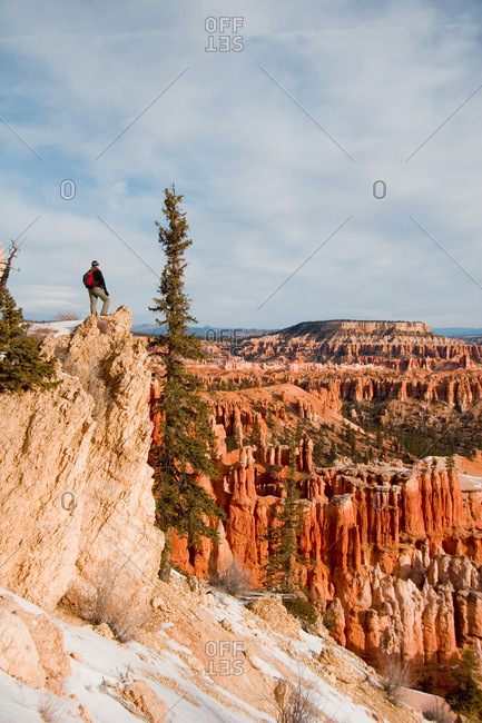 A solitary hiker looks out over the Bryce Amphitheater from a cliff.