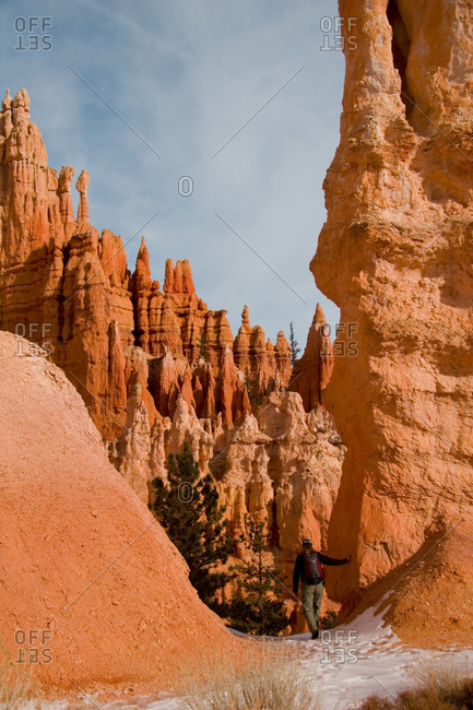 A woman walks along a snowy trail amongst the hoodoos and eroded cliff