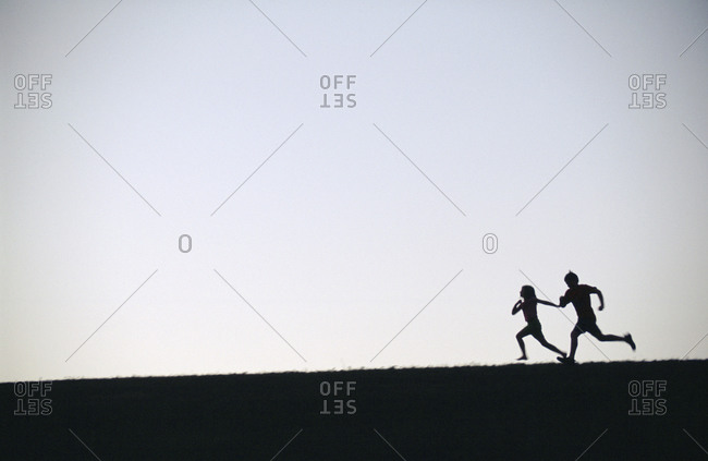 Two children are silhouetted as they chase each other along the dam at Holmes Lake Park in Lincoln, Nebraska.