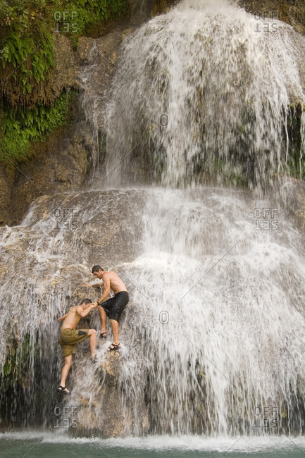 A man helps another climb onto a waterfall.