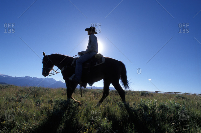A silhouetted cowboy rides in the evening on Lost Creek Ranch in Moose, Wyoming.