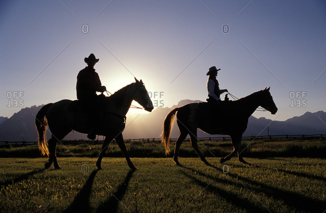 Silhouetted cowgirl and cowboy ride in the evening on Lost Creek Ranch in Moose, Wyoming.
