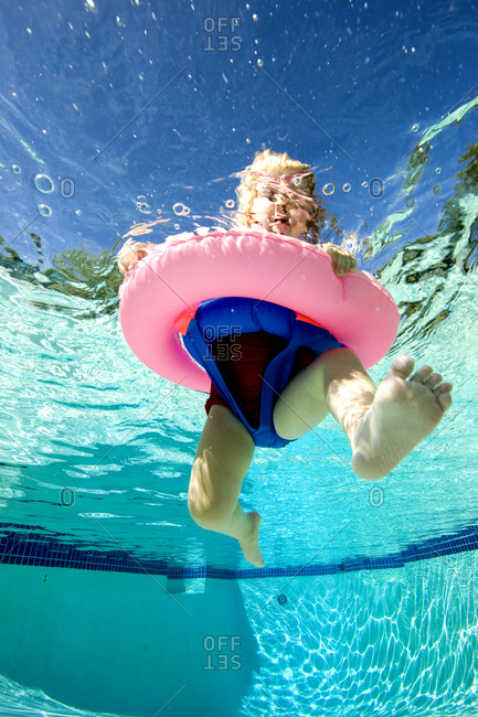 A baby girl floats in an inner tube in a swimming pool.