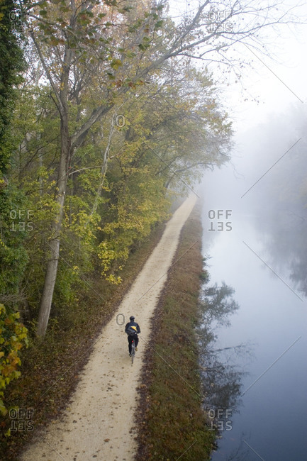 Bicyclist riding to work on the towpath in the morning mist