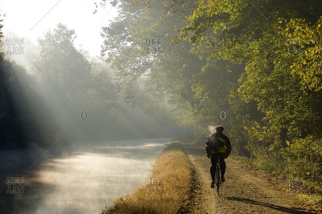 Bicyclist riding to work on the towpath in morning mist
