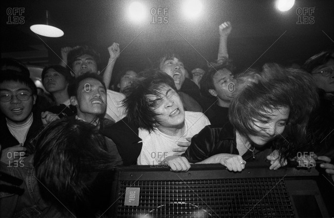 Beijing, China - May 23, 2014: Young people head banging during live show at a club