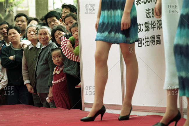 Shanghai, China - May 23, 2014: People watching an outdoor fashion show in a central shopping district