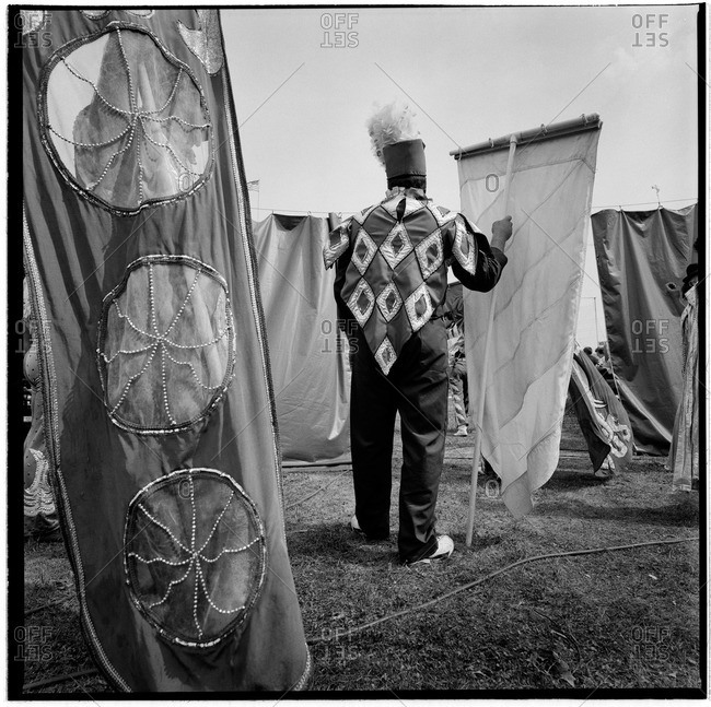 Circus performer walking with a banner