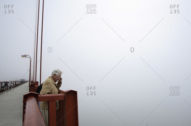 San Francisco, California, USA - June 2, 2006: Man looking down from the Golden Gate Bridge in foggy weather