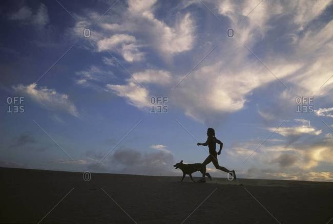 A woman and her dog run along the beach with  beautiful sky