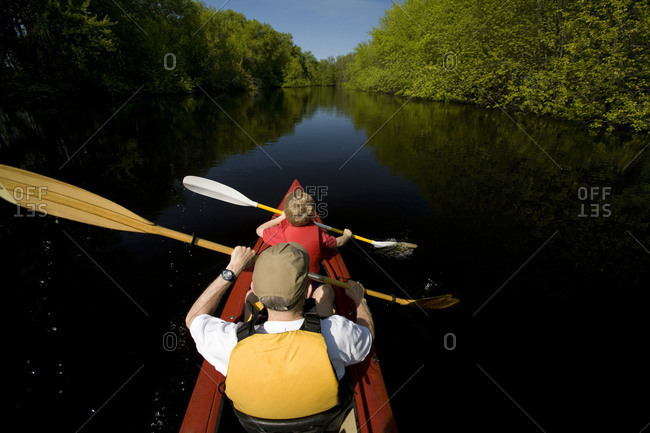 Father and son kayaking in river.