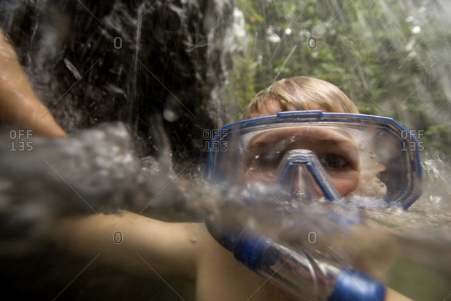 A boy swims and snorkels under a small waterfall in the rain forest.