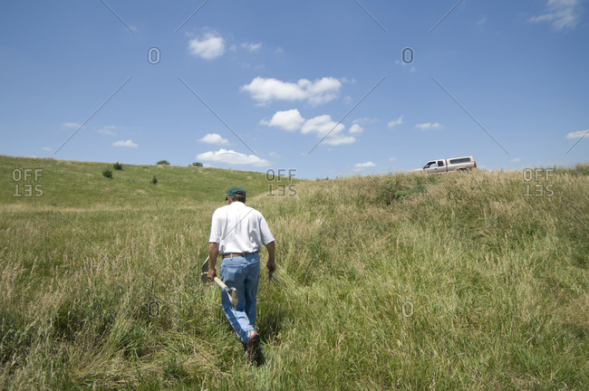 A farmer carries a shovel on a pasture in Valparaiso, Nebraska.
