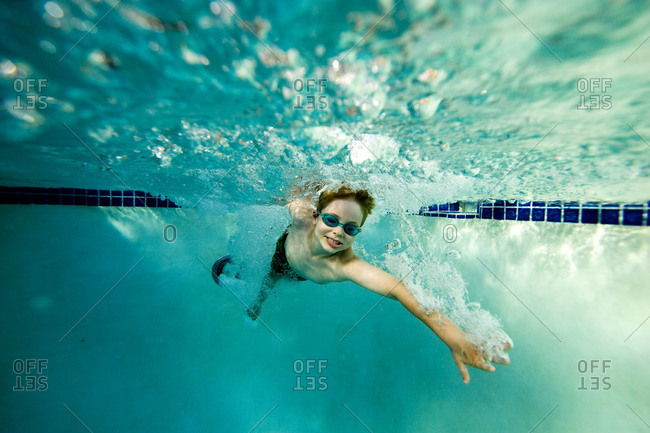 Seven year old boy swimming in a pool.
